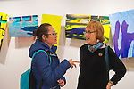 Huntington, New York, U.S. - March 1, 2014 -  At right, the wife of artist Thom O'Connor discusses his exhibit 'Hung Out To Dry' with a visitor at the Opening Reception '3 Wild & Crazy Artists' at FotoFoto Gallery.