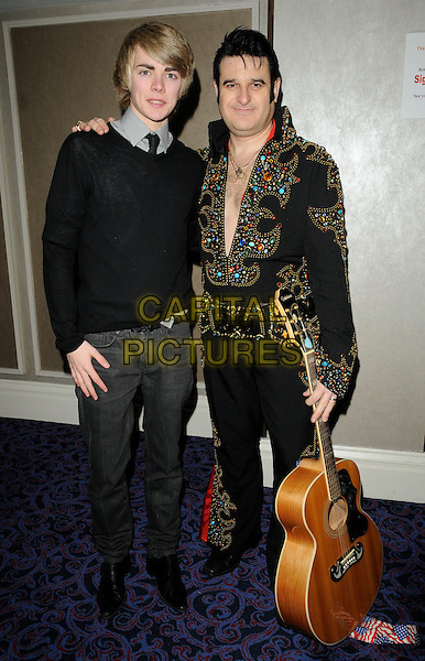 THOMAS LAW .attending the 'Mad Hatters Tea Party' event organised by London Taxi Drivers Fund for Underprivileged Children at the Grosvenor House Hotel, Park Lane, London, England, UK..January 31st 2010..full length black tie sweater jumper jeans  guitar Elvis impersonator look-a-like grey gray .CAP/CAN.©Can Nguyen/Capital Pictures