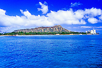 Diamond Head from the ocean with fluffy white clouds above