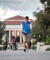 A student checks his phone while carrying a book in the quad, in front of Thorne Hall, on a cloudy Fall day, Nov. 3, 2015.<br />
