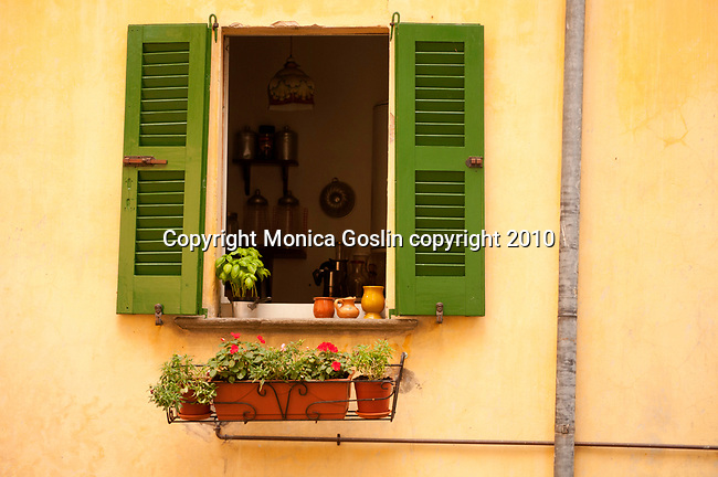 Green Shuddered window with pots and flowers in Naggio, a mountain town near Menaggio on Lake Como Italy
