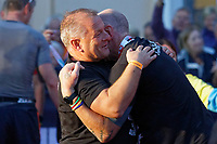 Pictured: Gareth Thomas is embraced by his husband Stephen (L) as he crosses the finish line. Sunday 15 September 2019<br /> Re: Ironman triathlon event in Tenby, Wales, UK.