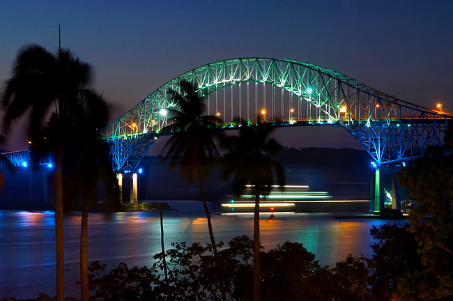 At dusk a ships' lights are in motion as it passes under the Bridge Of The Americas, the Pacific entrance to the Panama Canal in Panama.