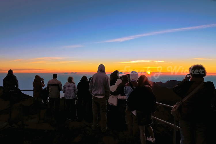 Male and female tourists enjoy the sunrise atop the Haleakala crater on Maui in Hawaii USA