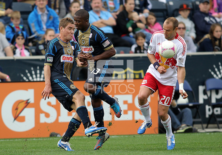 CHESTER, PA - OCTOBER 27, 2012:  Michael Lahoud (13) gets out of the way of Chris Albright (3) of the Philadelphia Union as he sends the ball past  Joel Lindpere (20) of the New York Red Bulls during an MLS match at PPL Park in Chester, PA. on October 27. Red Bulls won 3-0.