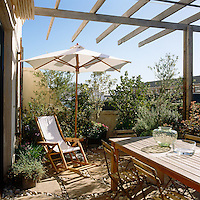 On this spacious roof terrace there is plenty of room for the lush vegetation growing in a series of terracotta planters
