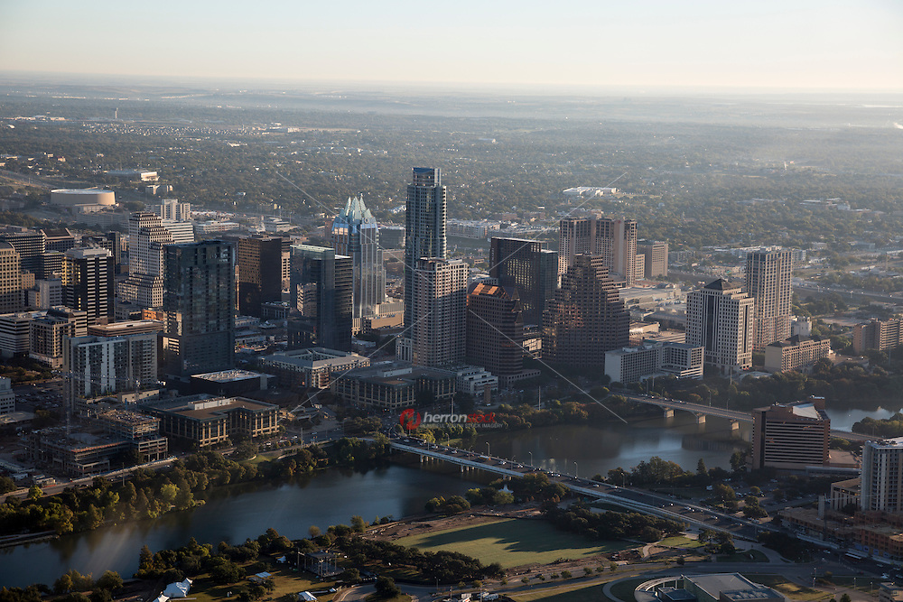 Aerial view from a helicopter of the morning sunrise over the heart of downtown Austin skyline and Lady Bird Lake with S. 1st Street and Congress Ave. Bridges.