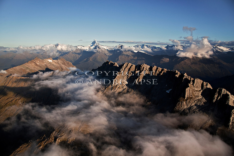 Aerial of Mount Aspiring. Jagged peaks and layer of cloud in foreground.   Westland Region. New Zealand.