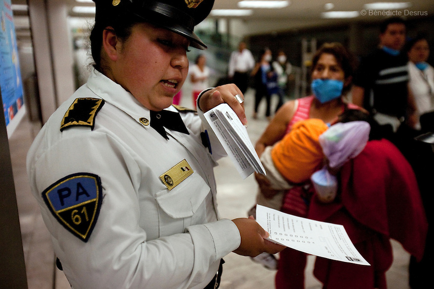 April 25, 2009 - Airport, Mexico City, Mexico - A police officer passes out surveys forms to people at the Mexico City airport to see if they are sick from the swine flu. Photo credit: Benedicte Desrus / Sipa Press