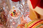 Over the shoulder of close up of a 4 month old infant, caucasian, with Santa hat on, reaching for ornament, hands visible, reflected in the silver glass ball Christmas ornament, ornament is hanging on a 60's retro aluminum christmas tree, selective focus.