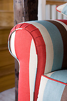 A detail illustrating the fresh red, white and blue stripes in the fabric used to upholster a living room sofa
