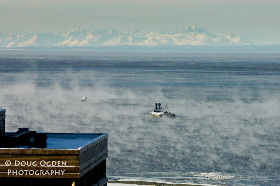 Steam rising from ice cold Cook Inlet, The Alaska Range are in the background Anchorage, Alaska