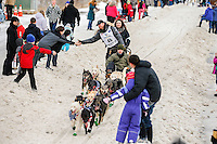 Justin Savidis runs down Cordova Street giving high-fives to spectators during the Ceremonial Start of the 2016 Iditarod in Anchorage, Alaska.  March 05, 2016