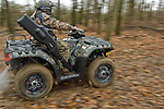 Pan shot of hunter on ATV in fall leaves