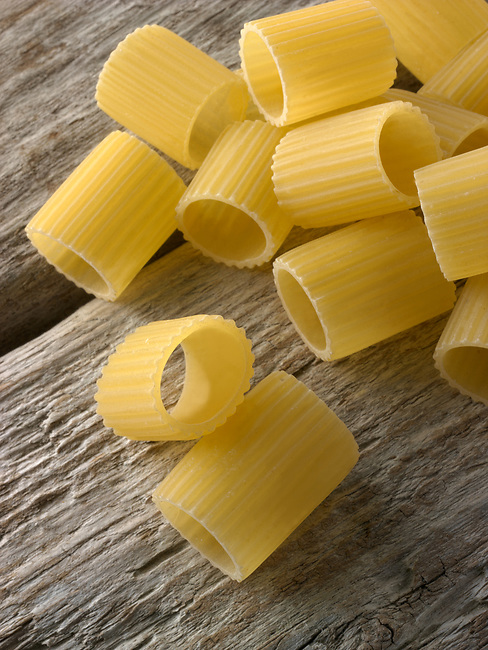 Traditional dried  Italaian Mezze Maniche Rigate pasta close up in a rustic setting on wood