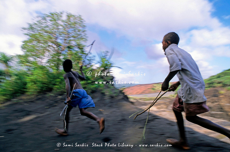Two young boys running, Sulphur Bay Village, Tanna Island, Vanuatu.
