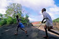 Two young boys running, Sulphur Bay Village, Tanna Island, Vanuatu.