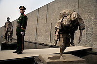 "A soldier stands guard near sculptures outside the Memorial Hall of the Nanjing Massacre in Nanjing, China, on Dec. 13, 2007.  After two years of renovations, the Memorial Hall of the Nanjing Massacre reopened to the public on Dec. 13, 2007, the 70th anniversary of the 6-week massacre by Japanese troops that started Dec. 13, 1937 and claimed more than 300,000 lives.  The commemoration comes amid renewed controversy about the accuracy of historical accounts of the massacre.  The massacre is also known as ""The Rape of Nanking."""
