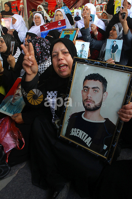Palestinian women hold pictures of jailed relatives during a protest calling for the release of Palestinian prisoners from Israeli jails at the Red Cross office in Gaza City on March. 7,2011. Photo by Ashraf Amra