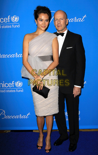 EMMA HEMING & BRUCE WILLIS .UNICEF Ball held At The Beverly Regent Hotel, Beverly Hills, California, USA, .10th December 2009..full length black bow tie tux tuxedo married couple husband wife grey gray one shoulder dress beige ruched clutch bag open toe shoes .CAP/ADM/KB.©Kevan Brooks/AdMedia/Capital Pictures.