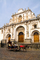 Colorful famous main church called Cathedral de Santiago with horse drawn carriage in tourist village of Antigua Guatemala