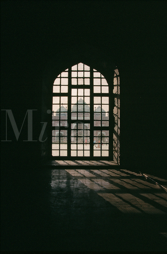 Interior view from the Taj Mahal as as light filters throught the window and into the tomb area. Agra, India.