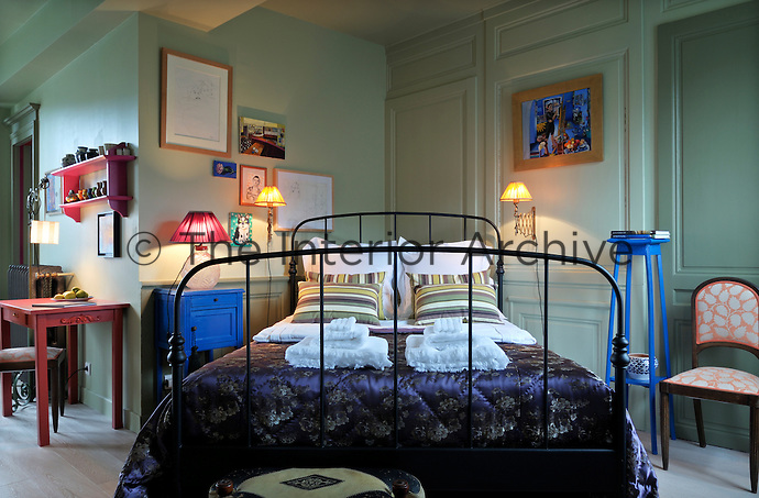 A wrought iron bed has been placed across the corner of the bedroom with occasional furniture painted in red and blue