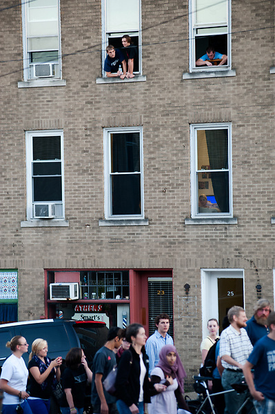 Ohio University students on west Washington street  watch marchers pass beneath their windows during the Interfaith walk which was hel in commemeration of 9/11. Photo by: Ross Brinkerhoff