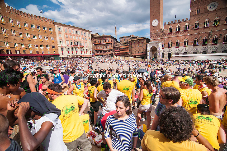 people slowly gathering inside the piazza del campo before the start of the palio di siena