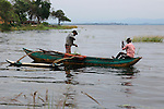Men fishing from an outrigger canoe, in reservoir lake, Polonnaruwa, Central Province, Sri Lanka, Asia