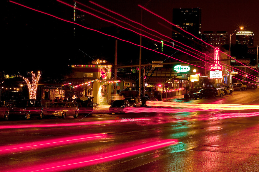 Cars leave light trails as the drive on the ever hip South Congress Avenue in Austin, Texas - Stock Image.