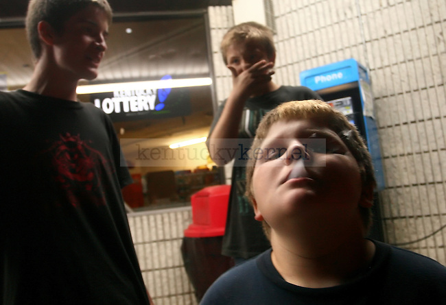 """William Slone, 11, french inhales from a cigarette while hanging out with his cousin Johnthan Everage, 11, and Joseph Short, 13,  outside of the Mi-Dee Mart after midnight in downtown Hindman, KY.  """"There isn't much to do in Hindman,"""" says Short."""