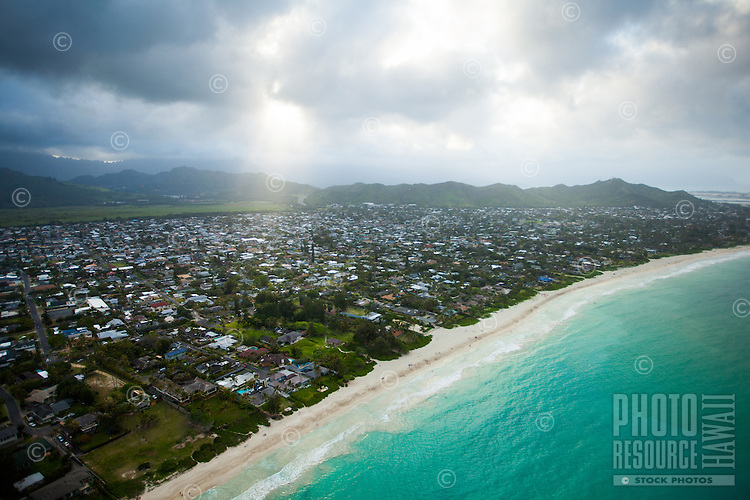 A big ray of light shines through the clouds onto Kailua and its beach, with Kane'ohe in the distance, Windward O'ahu.