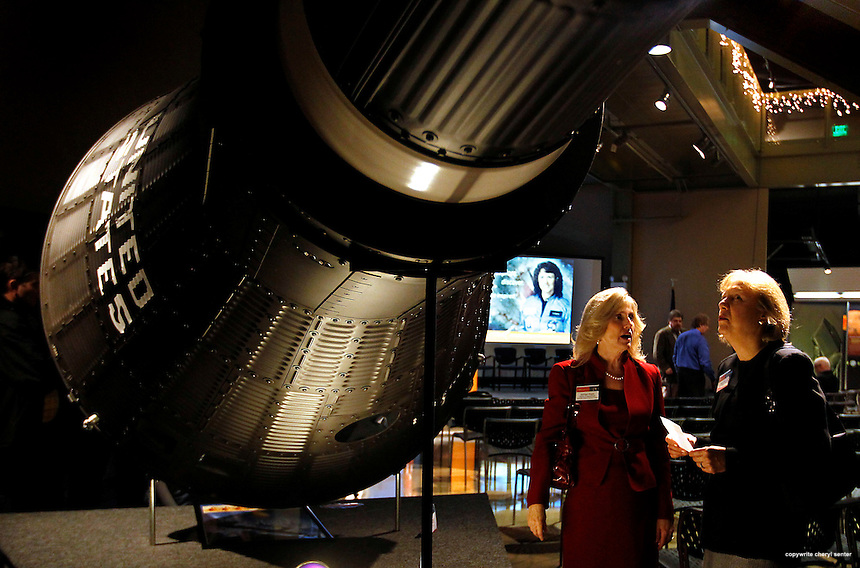 Standing next to a full-sized model of the capsule that took Alan Shepard to space are Discovery Center Director of Development Kathleen Regan, left, and, Betsy Brew, right, a VP from Fidelity Investments of Merrimack, N.H., (sponsor of event), during a special event held in recognition of the 25th anniversary of the space shuttle Challenger's launch and celebration of Christa's life and legacy at the McAulife-Shepard Discovery Center in Concord, N.H., Friday Jan. 28, 2011.  (AP Photo/Cheryl Senter) .