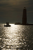 Sunset with fishermen on Lake Michigan, behind the Frankfort North Breakwater lighthouse, Frankfort Michigan.