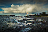Regnmolm med regnbåge vid strand på Torö i Stockholms skärgård.