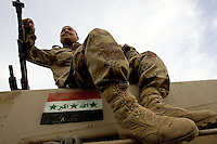 an Iraqi tanker from the 1st company, 1st armour battalion of the 1st mechanized Iraqi Army Brigade takes a break on the top of his tank after a long mission   while conducting  patrols, check points and observation posts on code name route Michigan, the main road of Ramadi in the week during the national election on TUE Dec 13 2005 in Ramadi, Iraq. 1st company is part of the first armor battalion of the New Iraqi Army. it has started its training in January 2005. after 50 days their 35 russian and chinese built T 55 tanks begun conducting operations under the guidance of a US military adivisor team. in April 2005 they patrolled in the Abu Ghraib area concluding their first significant mission. While these old tanks are rolling on the ramadi streets more modern T72s are getting ready to become fully operational in Taji, their main base. the Iraqi army wanted to show their power in ramadi during the Dec 15 elections displaying their new armour company. but like all the other Iraqi forces they are not going to secure the polling sites, staying in the rear with the rest of the iraqi and coalition forces. T 55s are very old tanks. production begun in the late 50s to the late 70s. athough obsolete many countries still use the T55 as their main heavy armoured combat vehicle. slow, heavvy and with very little room for the crew it suffers from many mechanical problems constantly challenging the iraqi mechanics and engineers.
