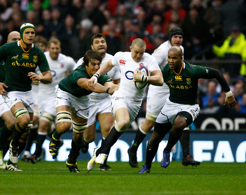 Photo: Richard Lane/Richard Lane Photography. England v South Africa. QBE Autumn Internationals. 24/11/2012. England's Mike Brown breaks from South Africa's Fancois Louw.