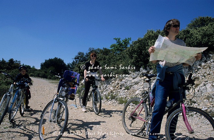 Family of cyclists stop to check their way on a map.