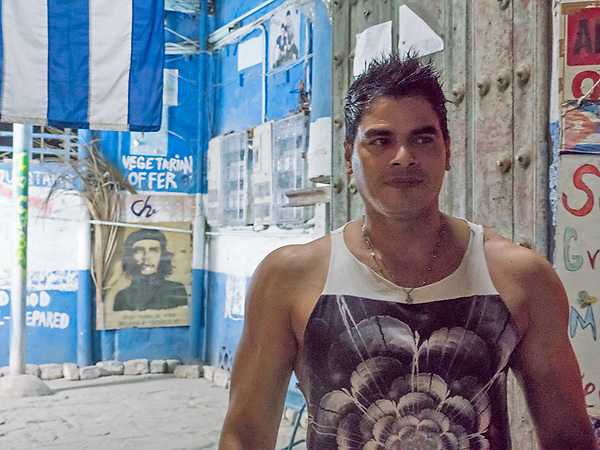 Young man on the street at night, with Che watching, La Habana Vieja