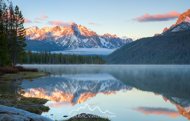 Idaho, Southcentral, Stanley. Morning light touches the Sawtooth Range and reflects the mountains in the calm misty waters of Redfish Lake in late Spring.