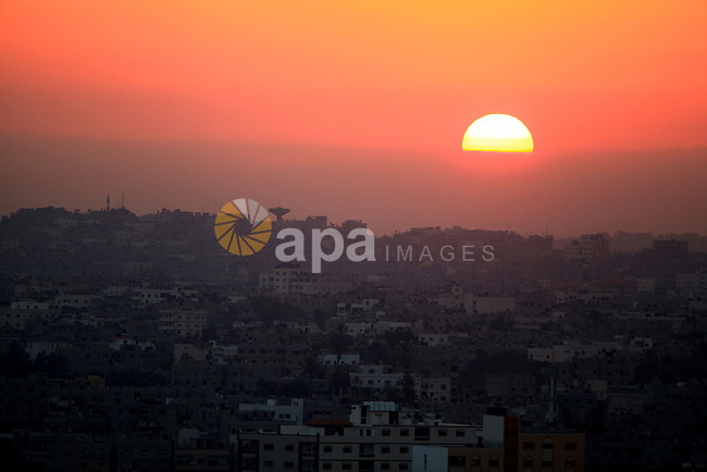 A picture shows the sun rising over Gaza city on August 11, 2014. Palestinian and Israeli negotiators on Sunday said they had accepted an Egyptian proposal for a new 72-hour truce with Israel, clearing the way for a possible resumption of talks on a long-term cease-fire arrangement in the Gaza Strip. Photo by Mohammed Othman