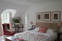The simple master bedroom is decorated with a collection of woodcut prints and an Indian quilt on the bed