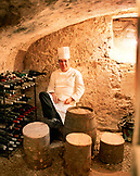 FRANCE, Auxerre, Yonne, Burgundy, portrait of chef Jean-Luc Barnabet sitting in wine cellar at his restaurant Jean-Luc Barnabet