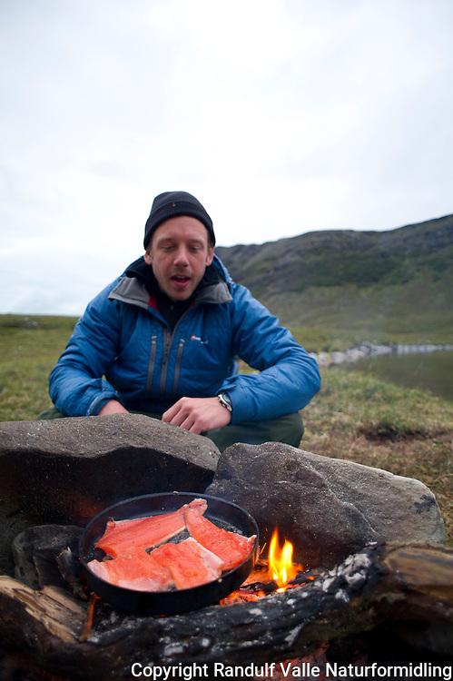 Mann steiker røyefileter på bål. ---- Man frying filets of arctic char.