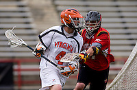 Matt White (4) of Virginia is defended by Bryn Holmes (17) of Maryland during the ACC men's lacrosse tournament finals in College Park, MD.  Virginia defeated Maryland, 10-6.