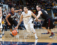 December 29th, 2012: California's Justin Cobbs drives through between Harvard defenders during a game at Haas Pavilion in Berkeley, Ca Harvard defeated California 67 - 62