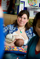 "A mother breastfeeding her baby at a drop-in breastfeeding support centre.<br /> <br /> Image from the ""We Do It In Public"" documentary photography project collection: <br />  www.breastfeedinginpublic.co.uk<br /> <br /> Dorset, England, UK<br /> 17/04/2013"