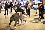 © Joel Goodman - 07973 332324 . Manchester , UK . 05/04/2015 . A man grabs another man by the legs as the two dance on the pavement on Withy Grove in Manchester City Centre . Revellers on a Saturday night out during the Easter Bank Holiday weekend . Photo credit : Joel Goodman
