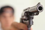 Teen (17 years old) boy pointing loaded handgun.   MR
